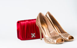 Woman gold shoes on background whit red purse. Woman gold shoes on white background whit red purse Royalty Free Stock Images