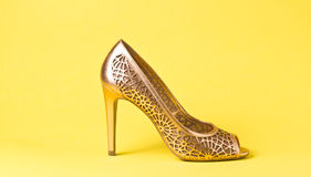 Woman gold shoes on background. Woman gold shoes on yellow background Stock Photos