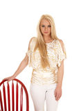 Woman gold zebra shirt stand by red chair Stock Photos