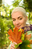 Woman with golden autumn leaves Stock Photo