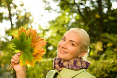 Woman with golden autumn leaves Stock Image