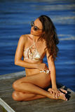 Woman in golden bikini and sunglasses  posing pretty on the wooden pier Stock Photography