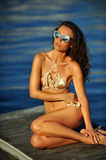Woman in golden bikini and sunglasses  posing pretty on the wooden pier Stock Photo