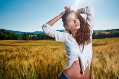 Woman on golden cereal field in summer Royalty Free Stock Photography