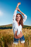 Woman on golden cereal field in summer Stock Photography