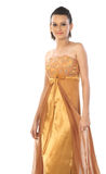 Woman with golden color long gown Stock Photos