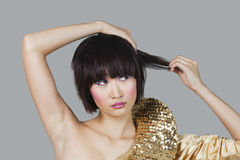 Woman in golden costume playing with hair over gray background Stock Photos