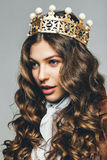 Woman in golden crown with curly hair. In studio stock images