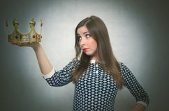 Woman with golden crown. Winner. First place concept. Woman is holding in hands a golden crown looks on it and is thinking. Winner. Authority Stock Images