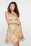 Woman in golden evening dress Royalty Free Stock Images