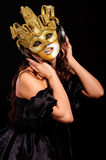 Woman in golden half mask Stock Image