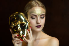 Woman with golden mask. Portrait of beautiful young girl with creative make up and big carnival mask in her hands, golden hairstyle. Louis court intrigues. Big Royalty Free Stock Photography