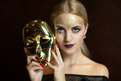 Woman with golden mask. Portrait of beautiful young girl with creative make up and big carnival mask in her hands, golden hairstyle. Louis court intrigues. Big Stock Photos