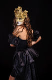 Woman in golden mask Stock Image