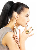 Woman with golden nails and beautiful gold jewelry Stock Image