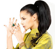 Woman with golden nails and precious stone emerald. Pretty woman with golden nails and beautiful precious stone emerald - isolated on white background stock photo