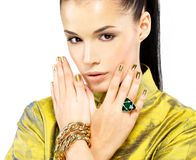 Woman with golden nails and precious stone emerald. Pretty woman with golden nails and beautiful precious stone emerald - isolated on white background royalty free stock photos