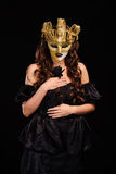 Woman in golden party mask. Portrait of sombre sexy woman in golden party mask isolated on black Royalty Free Stock Images