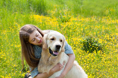 Woman and golden retriever in a field with flowers. Young beautiful girl hugging golden retriever dog on the field with yellow flowers on a summer day. Human Stock Photo