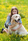 Woman and golden retriever in a field with flowers Royalty Free Stock Images