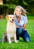Woman with golden retriever sitting on the grass Royalty Free Stock Photography