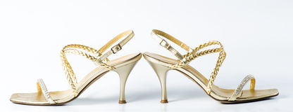 Woman golden shoes on white. Background Stock Photography