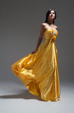 Woman in golden yellow dress Stock Image