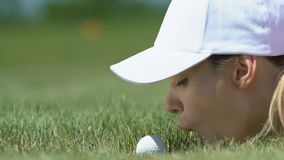 Woman golf beginner player lying on grass and blowing ball into hole, having fun stock footage