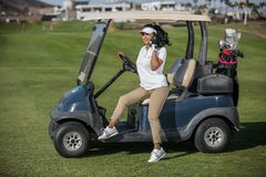 Woman in golf buggy speaking on phone. Young woman sitting on golf buggy on green field and having phone call in bright sunshine Royalty Free Stock Photography