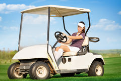 Woman in golf cart. Young attractive woman driving golf cart Royalty Free Stock Images