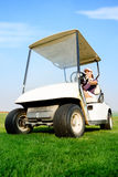 Woman in golf cart. Young female golfer driving golf cart Stock Photo