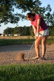 Woman on golf course. Hitting out of the sand Stock Photo