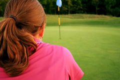 Woman on golf course. Lining up her putt Royalty Free Stock Photography