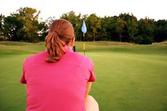 Woman on golf course. Lining up her putt Stock Images