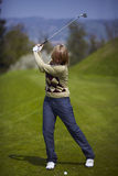 Woman on the golf course preparing for a swing. Woman golfer on the golf course preparing for a swing Stock Photos