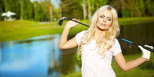 Woman with golf equipment. Young blonde  woman with golf equipment Royalty Free Stock Photos