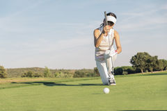 Woman golf player concentrating. Woman golf player concentrating for putting on green. Golf Concept Royalty Free Stock Image