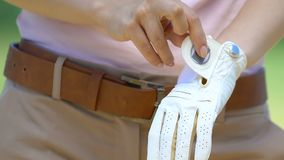 Woman golf player putting on and adjusting special leather glove before game. Stock footage stock video footage