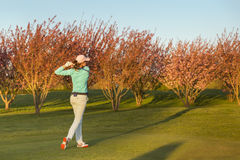 Woman golf player teeing-off. Royalty Free Stock Photo