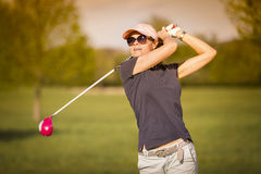 Woman golf player teeing off. Royalty Free Stock Photo