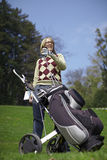 Woman with a golf trolley and clubs. Woman with a golf trolley and golf clubs on a course Royalty Free Stock Photos