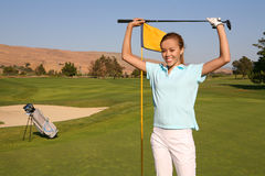 Woman Golfer. A pretty woman golfer retrieving her ball from the hole Stock Photography