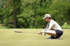 Woman golfer check line for putting golf ball on green grass royalty free stock image