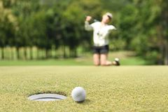 Woman golfer feeling disappointed after a putted golf ball missed. The hole stock image