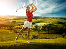 Woman golfer hitting the ball on the background scenery  beautiful Stock Photo