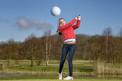 Woman golfer hitting the golf ball. With a driver in front of a water hazard on a golf course with the ball flying through the air towards the camera royalty free stock photography