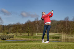 Woman golfer hitting a golf ball on the fairway Royalty Free Stock Photography