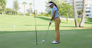 Woman golfer lining up for a putt. On the green viewed from the point of view of the flag in the hole Stock Photos
