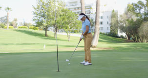 Woman golfer lining up for a putt. On the green viewed from the point of view of the flag in the hole Royalty Free Stock Image