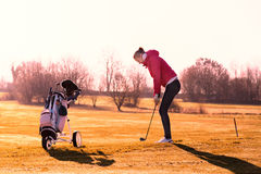 Woman golfer playing a round in evening sunlight. Woman golfer playing a round of golf in late evening sunlight lining up on the fairway for a shot with her golf Stock Photos